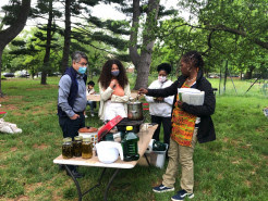 Nyambi Royster stirs a double boiler to melt wax for the herbal salve, while workshop attendees look on.