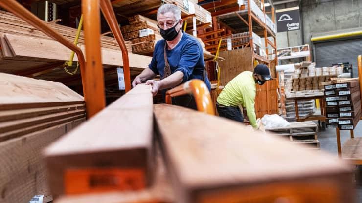 Employee piling wood onto a cart