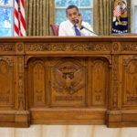 barack_obama_sitting_at_the_resolute_desk_2009