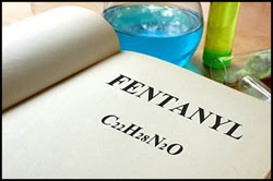 "The figure above is a photograph showing the word ""fentanyl"" written in a notebook along with its chemical makeup. The notebook is flanked by chemicals."