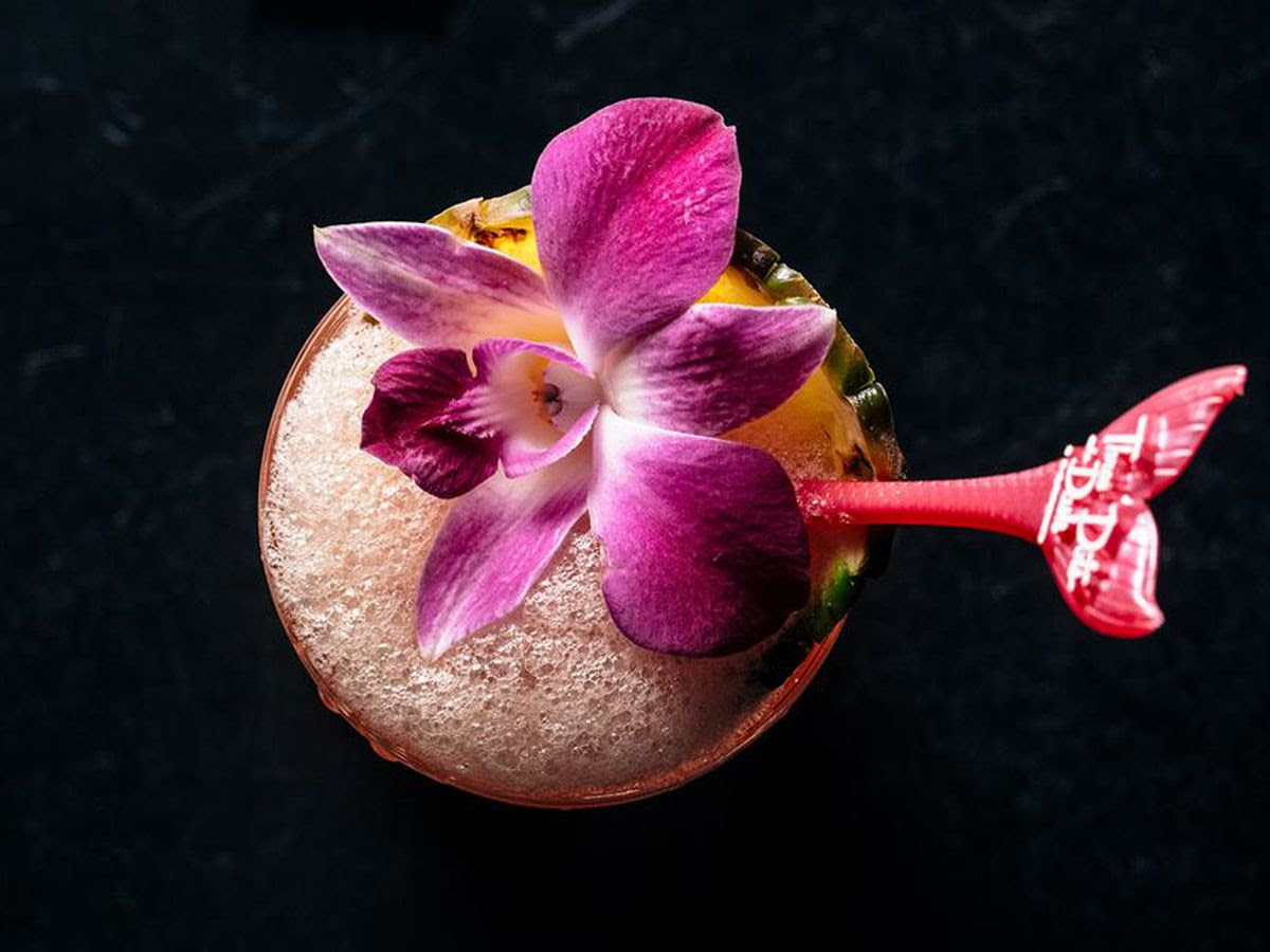 A cocktail with a pink flower
