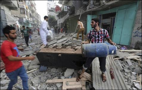 Unos hombres observan los daños en un edificio destruído durante un atáque aéreo del ejército israelí en la ciudad de Gaza.