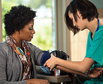 Healthcare professional checking the bloodpressure of a woman