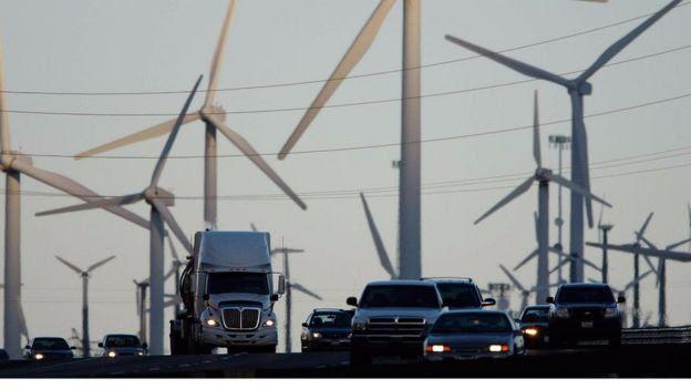 Veículos com torres de energia eólica ao fundo