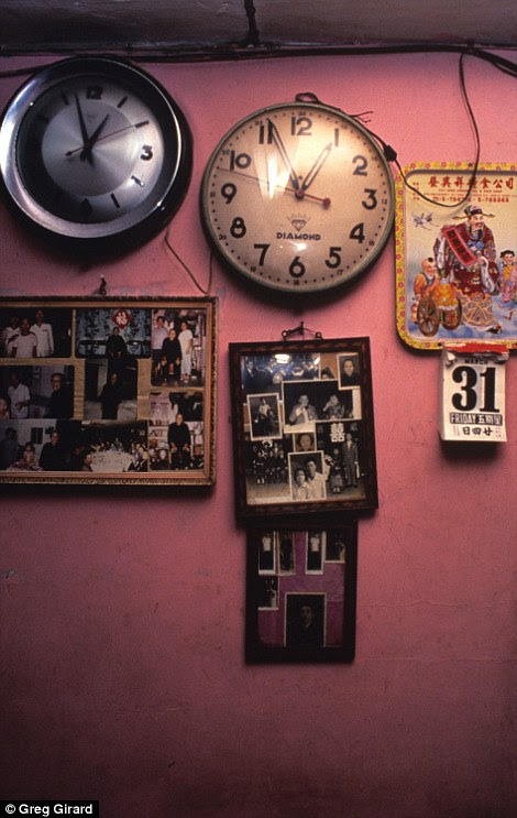 Clocks, family portraits and a calendar are displayed in a family home