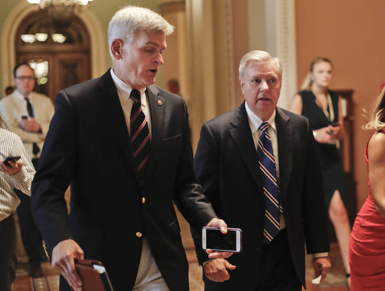 Sen. Bill Cassidy (R-La.), left, and Sen. Lindsey Graham (R-S.C.), right, talk on their way into a meeting at the Capitol. Graham and Cassidy are leading the new GOP charge, which would transform much of the Affordable Care Act into block grants and let states decide how to spend the money. (Pablo Martinez Monsivais/AP)