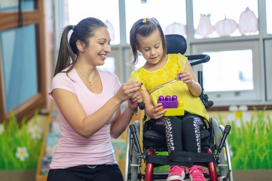 Caregive working with a child in a wheel chair