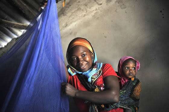 Mwajuma Ally Mandingo, 27, with her daughter Saidat, 9 months old, hangs a bed net in her house in Mtwara, Tanzania.