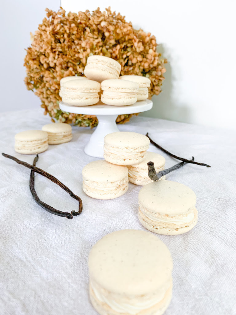 macarons on a pedestal with a hydrangea behind