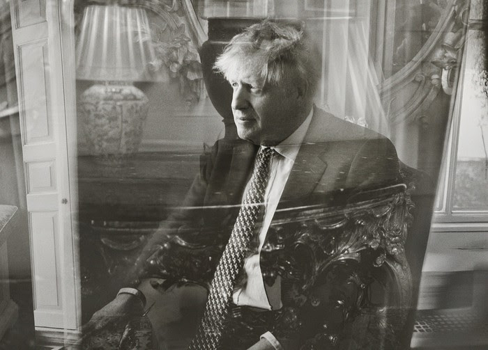 Photo: Prime Minister Boris Johnson seated, with a superimposed reflection through glass, 10 Downing Street, May 2021