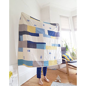 a photograph of a person holding a quilted blanket.