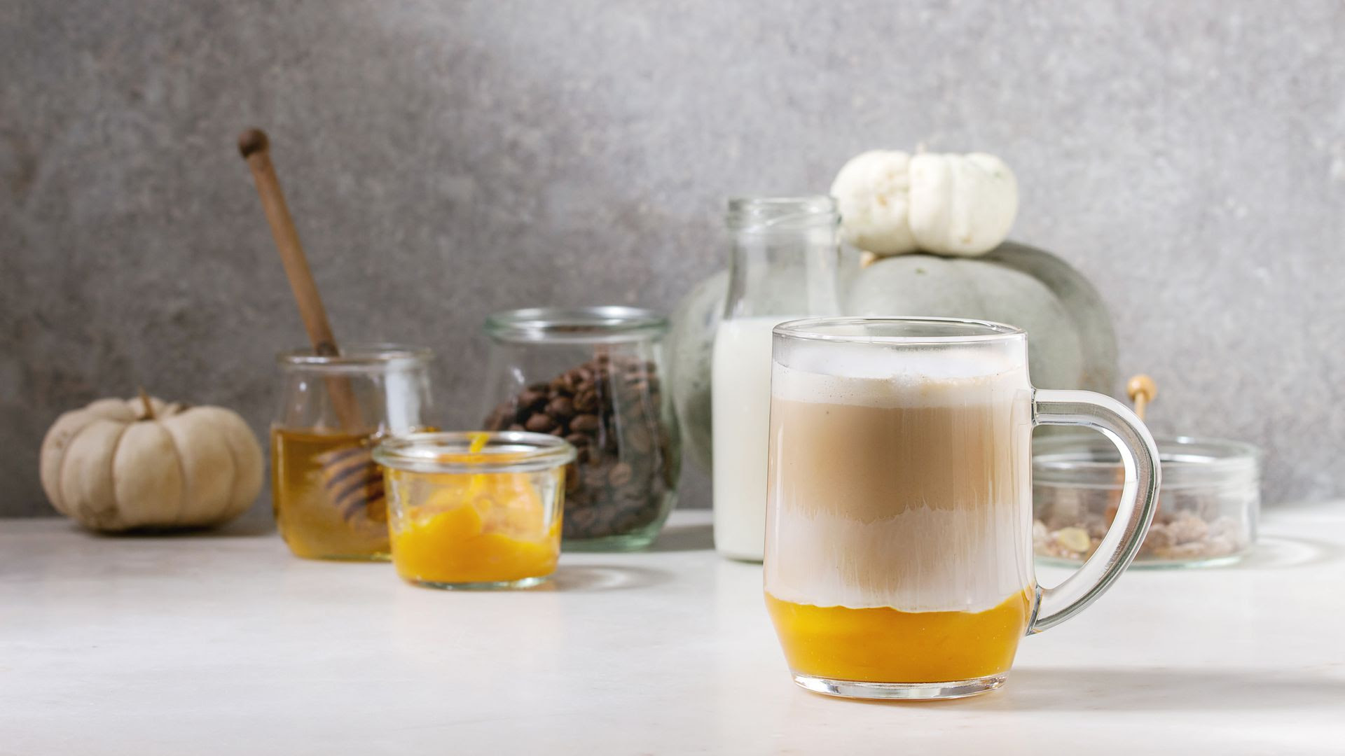 A glass of pumpkin spice latte together with some of its ingredients.