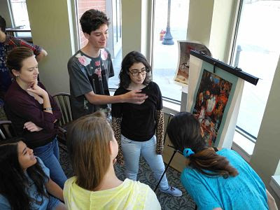 Students analyzing paintings at art lesson