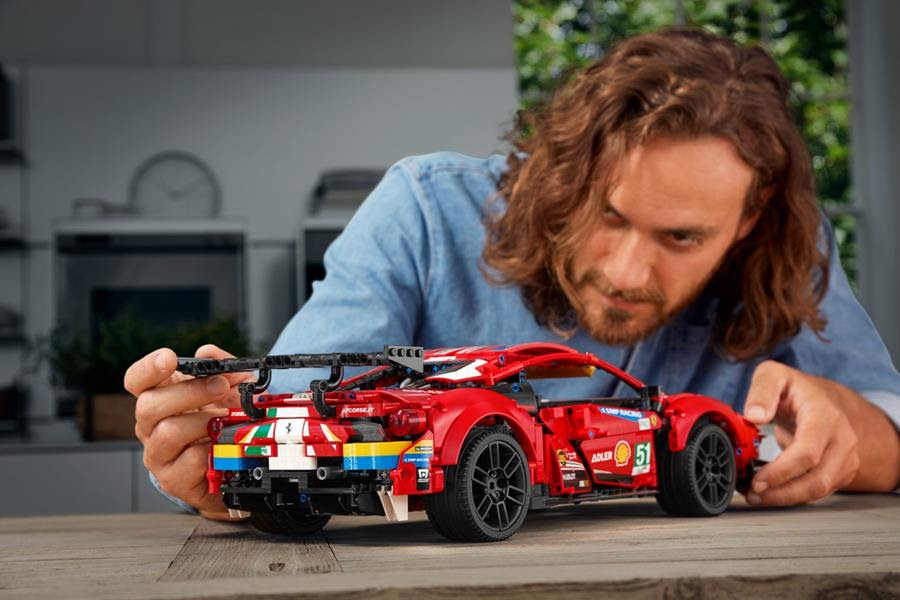 Image of a man looking at the LEGO model sitting on a table