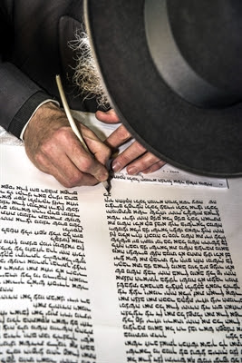 An Orthodox Jewish man writes a                 Torah scroll.