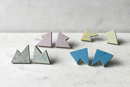 A photograph of four pair of earrings by Roslyn Leitch. They are displayed against a white marbled background, and are different colours, clockwise top to bottom: pink, light grey and yellow, grey and blue, and blue.