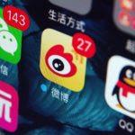 A gauche et à droite de l'écran d'un smartphone chinois, les icônes des applications de messagerie Wechat et QQ du groupe Tencent, et au centre, l'application de microblogs Weibo créée par Sina. (Crédits : Da qing / Imaginechina / via AFP)