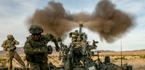 Army Spc. Eric Hayden fires an M777A2 howitzer while Staff Sgt. Robert Hartner braces to handle the shock of firing at the National Training Center at Fort Irwin, Calif., March 5th, 2020. - ALLOW IMAGES
