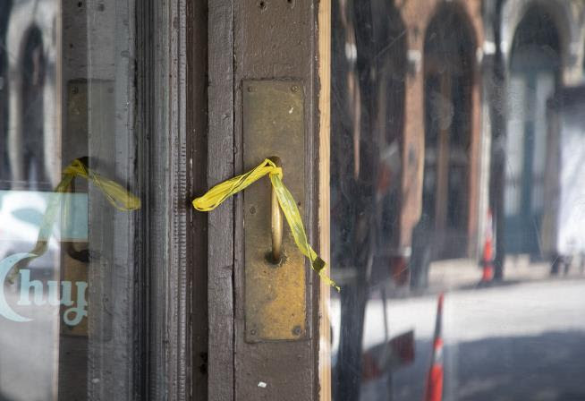 Caution tape is wrapped around a restaurant's door handle after a mass shooting