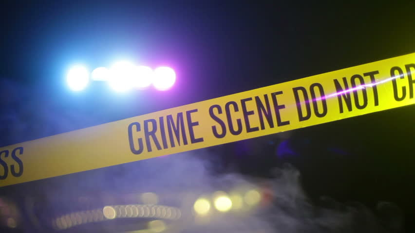 Crime scene tape with police lights in the background