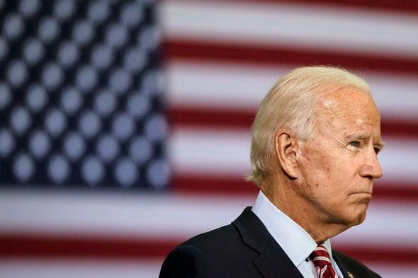 Joe Biden standing in front of an American flag