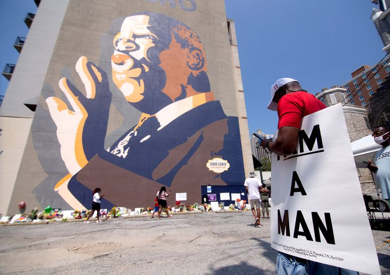 David Richardson holds a sign that reads I Am Man while visiting the John Lewis memorial under the John Lewis mural on Auburn Ave, Sunday, July 19, 2020. STEVE SCHAEFER FOR THE ATLANTA JOURNAL-CONSTITUTION