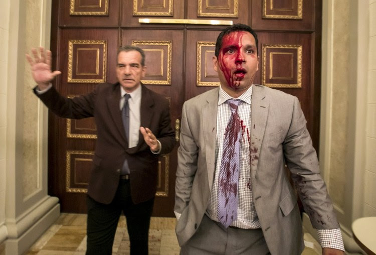 Venezuelan lawmaker José Regnault, his face bloodied, leaves the National Assembly with Deputy Luis Stefanelli after a clash Wednesday with demonstrators in Caracas, Venezuela. (Miguel Gutierrez/European Pressphoto Agency) </p>