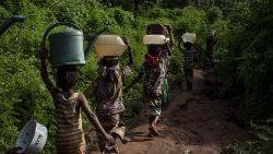 Mujeres transportan agua hacia sus hogares