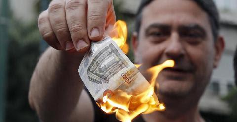 Dos personas queman unos billetes de euro en una manifestación anti austeridad frente a las oficinas de la Comisión Europea en Bruselas. REUTERS/Alkis Konstantinidis