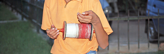 A picture of a young boy in an orange shirt holding a spindle of red string while is left hand grasps a section of the thin red string.