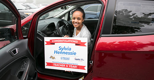 HCPSS Teacher of the Year Sylvia Hennessie sitting in her new car.