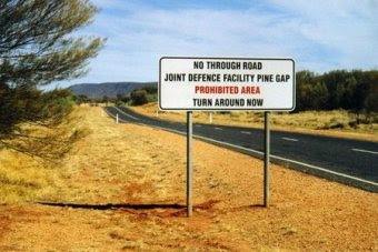 "A warning sign next to a road says ""No through road. Joint defence facility Pine Gap. Turn around now."""