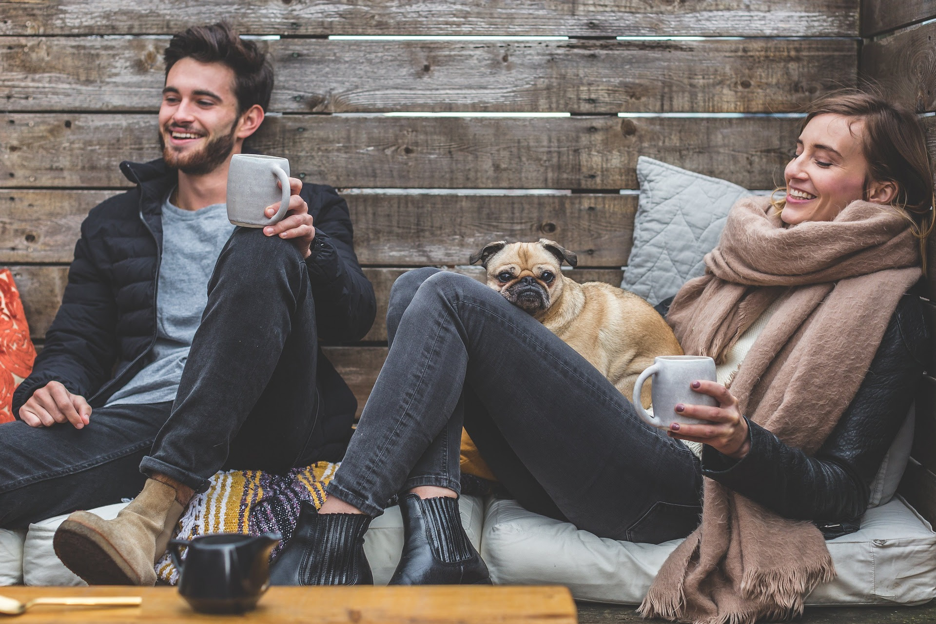 Image os a man and woman talking and drinking coffee with a dog