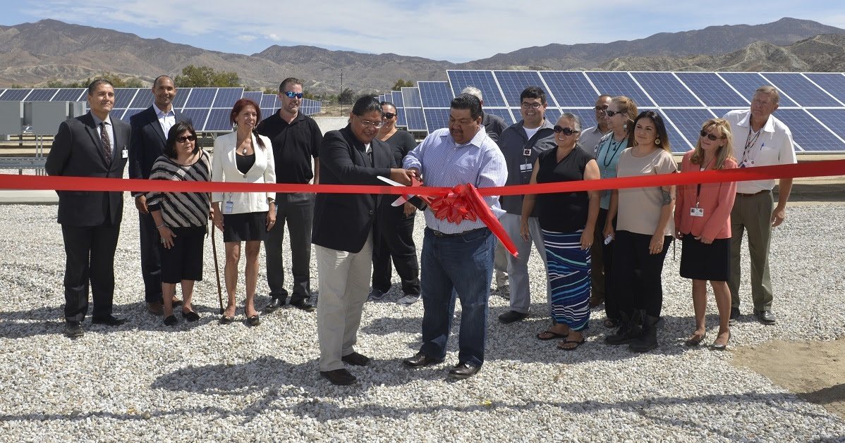 Photo of two men ribboncutting a solar project.