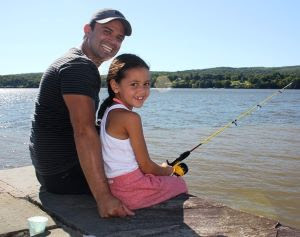A dad and his young daughter who is holding a fishing rod smile at the camera as they sit by the Hudson River.