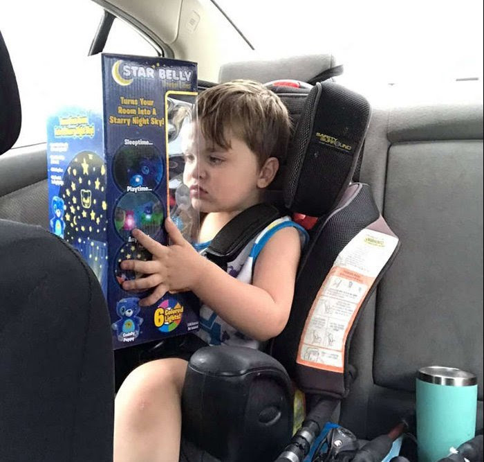 A child in a car seat holding a toy