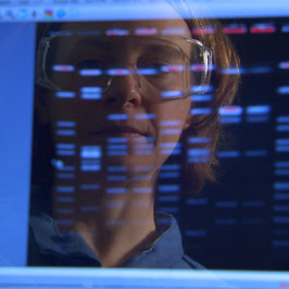 Photograph: Scientist's image is reflected on computer screen.