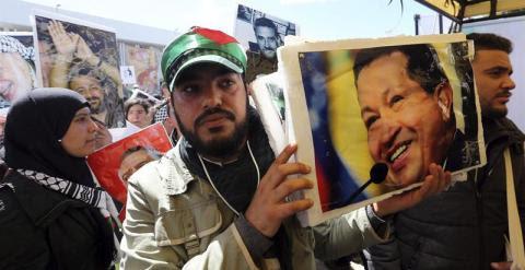 Un hombre sostiene el retrato del ex presidente venezolano Hugo Chávez a su llegada al XIII Foro Mundial Social (FMS).- EFE