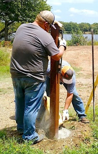 Mack Wood and Jay Barfield set a post for new fencing and gate to keep vehicle traffic off the Lake Nanih Waiya dam.