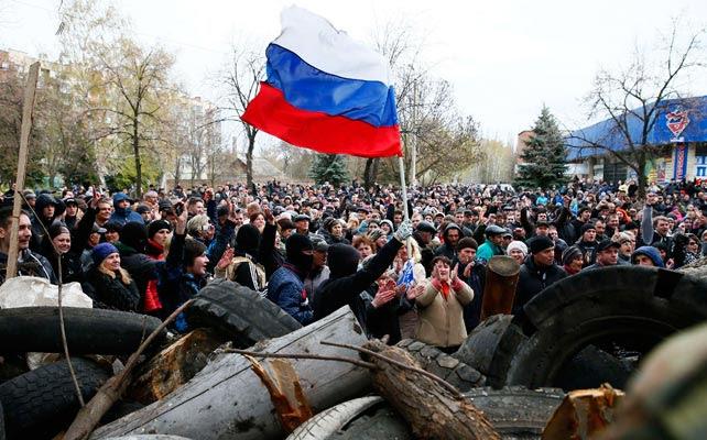 Prorrusos ondean una bandera rusa frente a la comisaría tomada en Slaviansk.