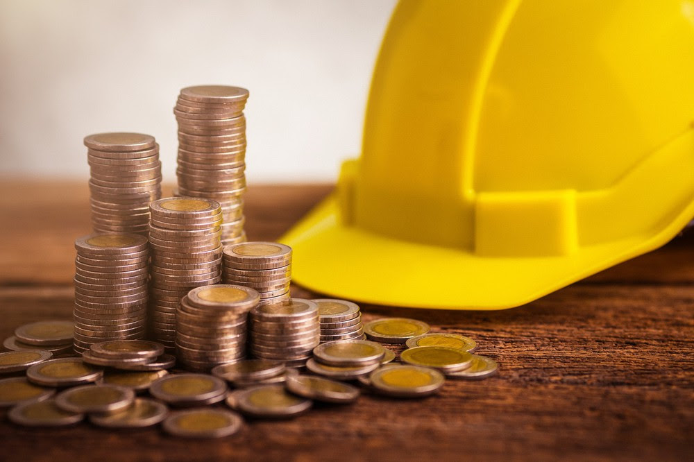 A hardhat behind a stacks of euros