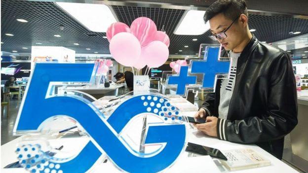 consumidor usa celular 5G em feira