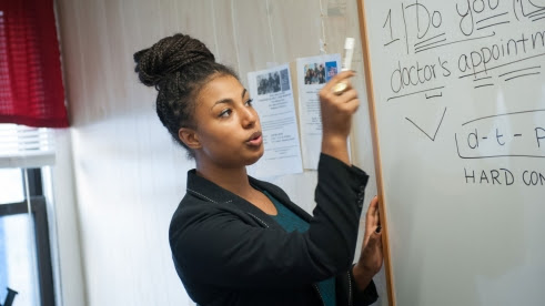 Woman using a white board.