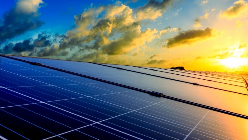 Photovoltaic solar panels and high voltage power lines at sunset sky background,green clean alternative energy.