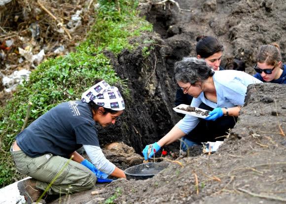 Arqueólogos trabajan en el campo del Batallón N° 13 donde encontraron restos de una persona. Foto: AFP