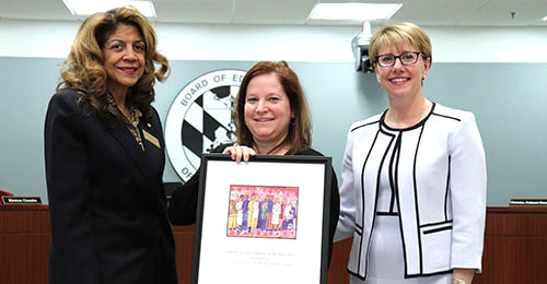 Debbie Engles being honored by the BOE Chair and the Deputy Superintendent.