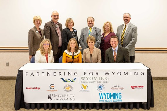 "University of Wyoming President Laurie Nichols sits with WDE Chief Academic Officer Shelley Hamel, Wyoming Community College Commission Executive Director Sandra Caldwell, and the presidents of all seven of Wyoming's community colleges at a ceremonial signing of the Memorandum of Understanding. A Banner includes everyone's logo and reads, ""Partnering for Wyoming."""