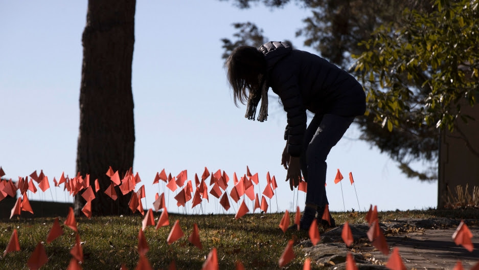A woman does maintenance on the construction flags in her front yard in Boise, Idaho, Feb. 10, 2021.