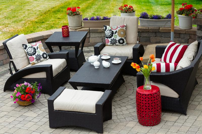 Overview of Upscale Patio Set Dark Wicker Luxury Furniture with Comfortable Cushions on Outdoor Stone Patio of Affluent Home