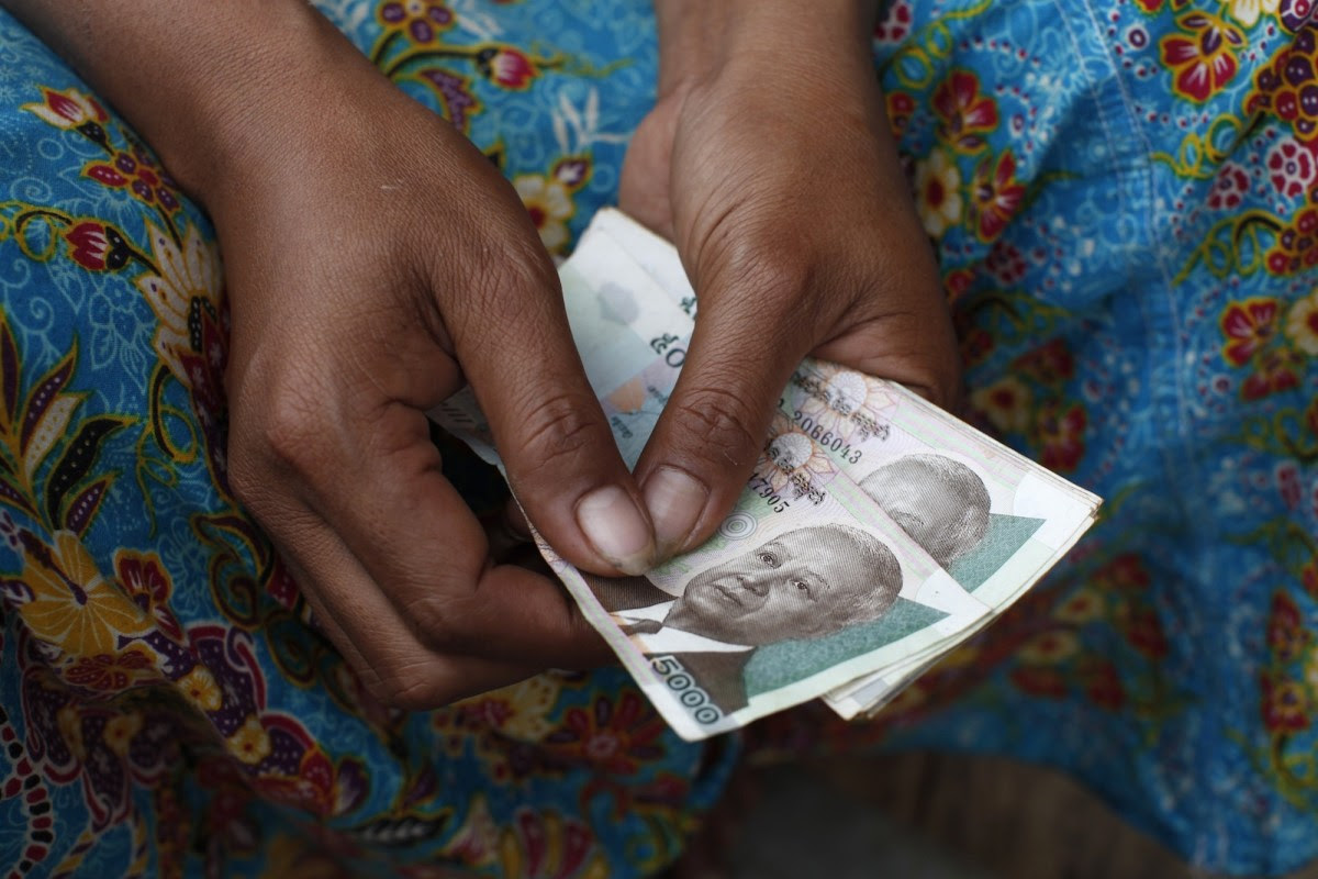 A Cambodian woman holds riel bank notes. Photo: AFP Forum